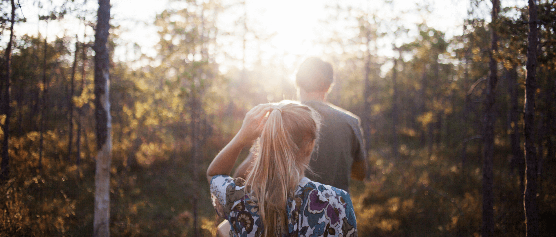 A young woman following a young man into the forest, summery atmosphere and sunshine, rear view